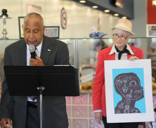 "LeRoy Heyliger, grandfather of Mattituck Junior High student Justin McKinney, reads his grandson's poem ""I am"" as the event's organizer, Susan Dingle, holds Justin's artwork."