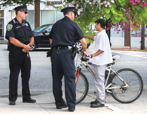 BARBARAELLEN KOCH FILE PHOTO | Riverhead police speaking to a Hispanic bicyclist on West Main Street in downtown Riverhead in 2009.