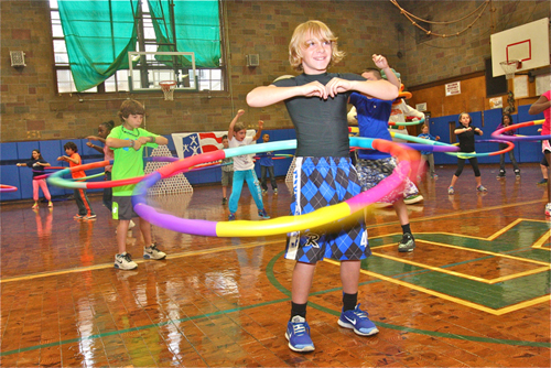 BARBARAELLEN KOCH PHOTO | Students participate in a Project Fit America exercise using weighted hula hoops.