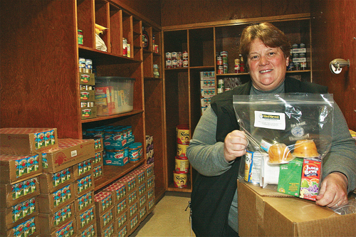 Phillips Avenue Elementary School principal Debra Rodgers holds a package of Island Harvest food that students take home in their backpacks for the weekend. The new food pantry opens today; hours will be from 6:30 to 8 p.m. the second and fourth Thursday of each month. (Credit: Barbaraellen Koch)