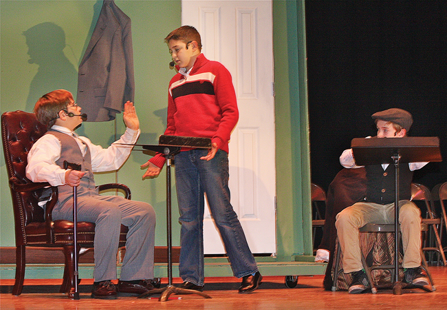Kyle Frost (from left) as Scrooge, Tanner Dispenziere (center) as Scrooge's nephew Fred and Jacob Raynor as Bob Cratchit rehearse a scene for the production of 'Scrooge.' (Credit: Barbaraellen Koch)