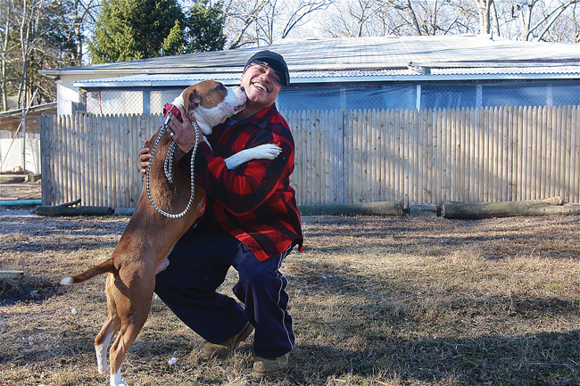 Kent Animal Shelter kennel manager Ricky Appling gets some kisses Friday from Yogi, a year-old pit bull mix, in the Calverton shelter's play yard. (Credit: Barbaraellen Koch)