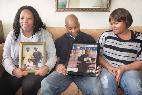 BARBARAELLEN KOCH PHOTO  |  Demitri Hampton's sister Jennifer Davis (left), brother Jamal Davis and first cousin Latisha Diego with photos of Demitri, who appeared on the cover of a Suffolk Community College campus magazine in 2012, during a meeting with reporters in Polish Town Tuesday.