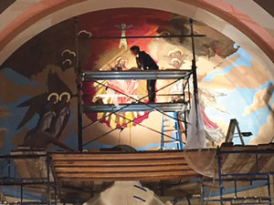 An artist works to repaint the main mural at St. Isidore. (Credit: Courtesy, Robert Kuznik)