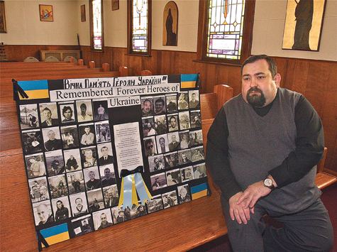 Father Roman Malyarchuk with the poster his parishoners made to honor those who were killed in the protests in Kiev, the capital of Ukraine. (Credit: Barbarallen Koch)
