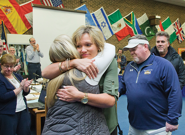 Kelli Cutinella (left), the mother of Shoreham-Wading River student Tom Cutinella, who died last year playing football, hugs Wildcat Athletics Club board member Regina McGee at a school board meeting Tuesady night. The booster club had just presented Ms. Cutinella with a $106,000 check to help start a foundation and scholarships in Tom's memory. (Credit: Paul Squire)