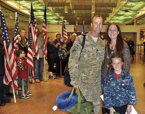 U.S. Navy Cmdr. Tim McAllister, his partner, Deanna Ziegler, and his 8-year-old daughter, Hollie, at his homecoming at MacArthur Airport Saturday night. (Credit: Courtesy photo)