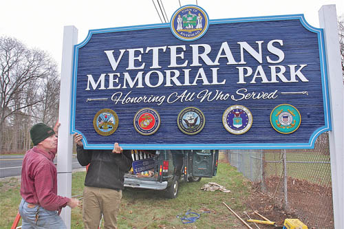 BARBARAELLEN KOCH PHOTO  |  Jim C. Seno (left) and his son Jim G. Seno of Wedel Signs install the Veterans Memorial Park sign Tuesday in Calverton. Two of the park's four ballfields are being named in memory of fallen soldiers (and Shoreham-Wading River High School graduates) Sergeant Jonathan Kelly and Sergreant First Class Anthony Venetz.