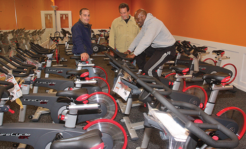 Maximus Health & Fitness owners Frank Distefano (from left) and Phil Durinck look on as personal trainer Greg Trent tries out one of the new LifeCycle GX spin bikes. (Credit: Barbaraellen Koch)