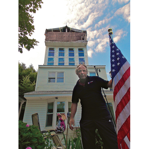 Eugene Lafurno pictured at his Baiting Hollow home, which he has dubbed 'The Epiphany.' Riverhead Town was given approval from a court last month to demolish the addition at the top of the house. (Credit: Joseph Pinciaro)