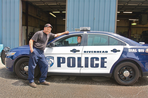 Mike Curtis, Riverhead Town's lead mechanic, with Officer Doug Geraci at the town's municipal garage, where Mr. Curtis spent 50 to 60 hours outfitting the department's new car for patrol use. (Credit: Barbaraellen Koch)