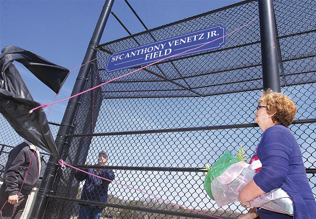 Marion Venetz (right) helping to unveil the sign naming field two at Veteran's Memorial Park in Calverton after her son during Little League opening day ceremonies lin 2013. (Credit: Barbaraellen Koch, file)