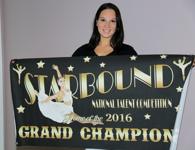 Ms. Latour poses with the grand champion banner at her home Friday. (Credit: Joe Werkmeister)