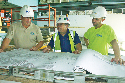 Keith DeLucia (from left), project manager with School Construction Consultants, Steve Uzzi, field supervisor for Stalco Construction in Islandia, and Sam Bailey, project manager for DeLuxe Building Systems of Pennsylvania, go over plans at the charter school. (Credit: Barbaraellen Koch)