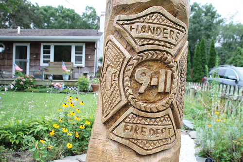 PAUL SQUIRE PHOTO  |  Artist Richard Anderson was commissioned to carve this tribute to Flanders' bravest in a tree in Sue Mastelli's front yard. Mr. Anderson also sculpted the works that line the boardwalk along the Peconic River in downtown Riverhead.