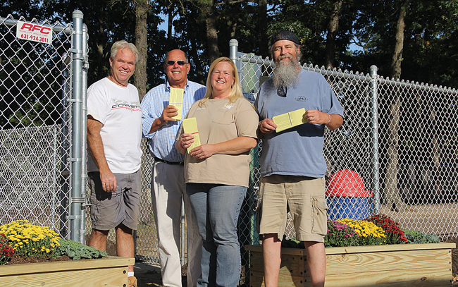 Riverhead Move the Animal Shelter volunteers (from left) Richie Cox, Fred McLaughlin, Denise Lucas and Lindsay Reeve at Stotzky Park's Duke Dog Park Friday. They're holding tickets to the group's three-year anniversary benefit at Suffolk Theater planned for November. (Credit: Carrie Miller)