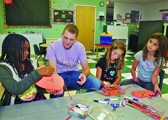 BARBARAELLEN KOCH PHOTOAnthony Mammina with students in after school care (from left) Eunique Trent, 10, Sophia Romeo,9, and Ava Cravotta, 9,  making decorations for the bulletin board at Kiddie Academy in Wading River Tuesday afternoon.