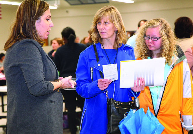 RIVERHEAD SCHOOLS COURTESY PHOTORiverhead High School student Kerri Koeberl (right) with her mother Michaela at the Transition Fair in 2014 speaking with one of the agency representatives who participated.
