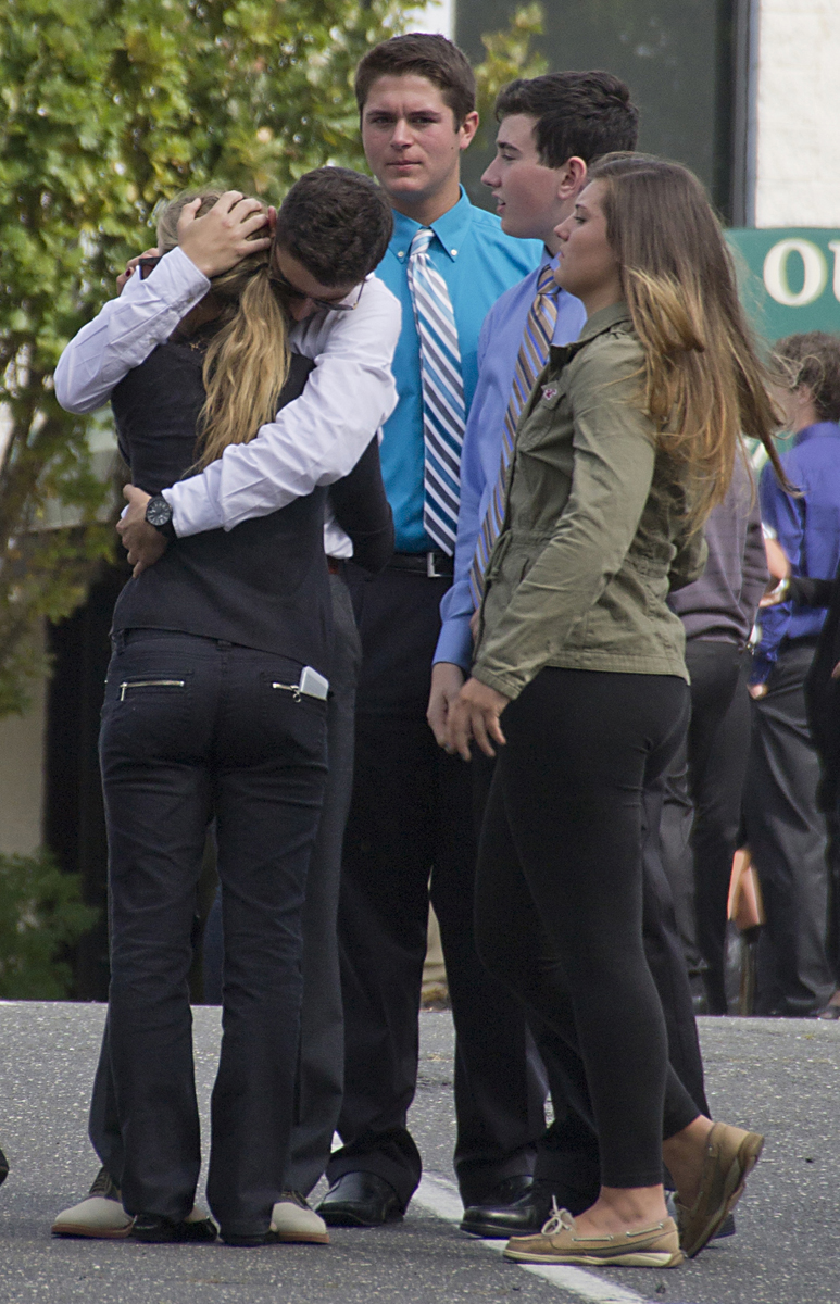 Friends embrace outside the funeral, where more than a thousand attendees paid their respects to Tom Cutinella. (Credit: Paul Squire)