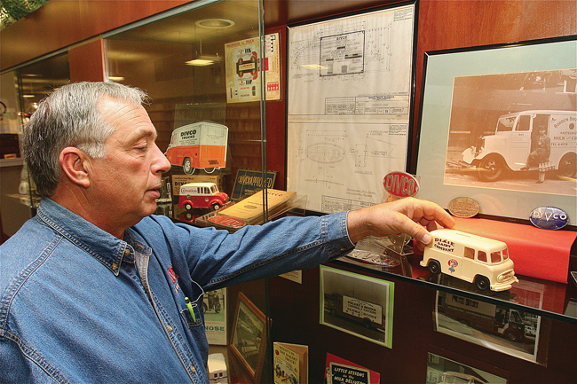 John Rienzo setting up his Divco memorabilia in the display case at Riverhead Free Library, where it is on view during October. (Credit: Barbaraellen Koch)
