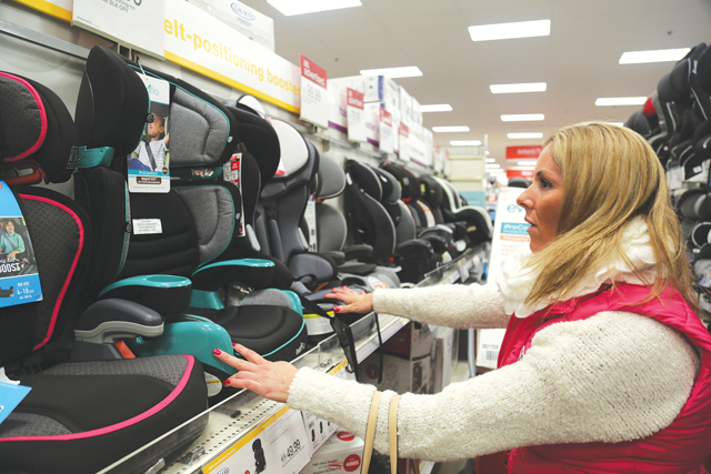 Ms. Byrnes inspects carseat models at Target Tuesday night, hoping to find more on sale. She said she's been surprised by the outpouring of support from friends and neighbors. 'It's rewarding how many people have offered to help,' she said. (Credit: Paul Squire)