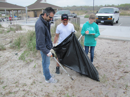 Konstantine Rountos and Celestino Pascual pick up trash while another student logs the type of trash.