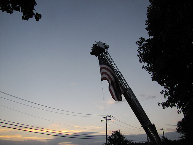 The Riverhead Fire Department hangs the American flag. (Credit: Tim Gannon)