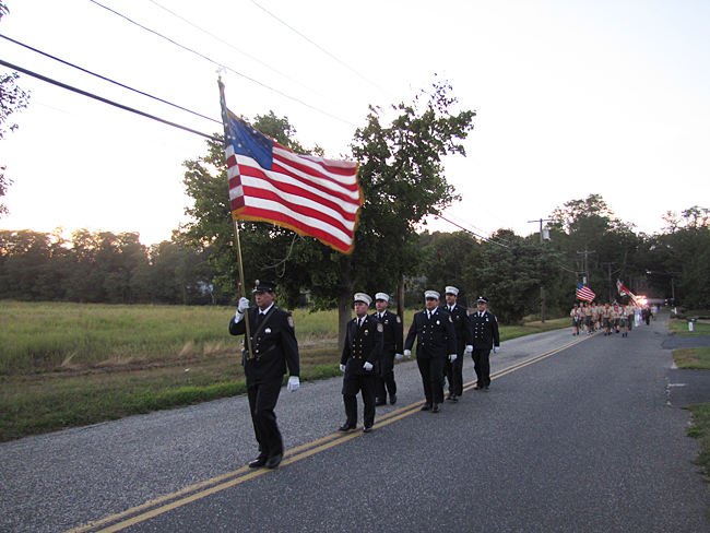 The Riverhead Fire Department marches down Park Road, with Wading River scouts behind them, at the Reeves Park memorial. (Credit: Tim Gannon)
