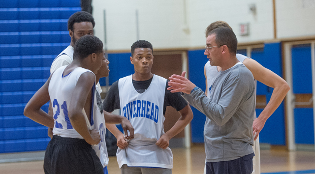 Riverhead coach John Rossetti goes over instructions at practice with several players last week. (Credit: Robert O'Rourk)