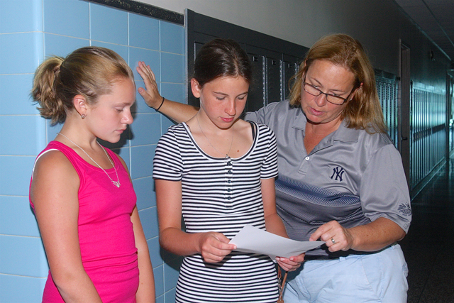 RMS Prtincipal Andrea Pekar helps seventh grade students Morgan Dunn and Skylar Wicklund find their classrooms on a tour of the building Monday.