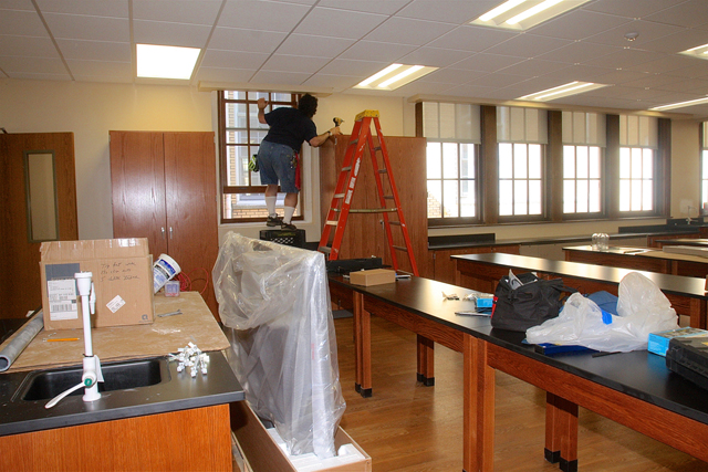 Pulaski Street School's custodian Claude Pragliola installs the shades in the new science lab.