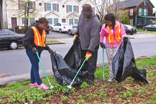 Craig Scott and his daughters Aneisha, 16, (left) and Shayla, 12, of Riverhead worked on cleaning up an empty wooded lot on the western end of Lincoln Avenue during last April's cleanup. (Credit: Barbaraellen Koch, file)