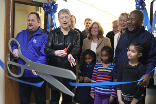JENNIFER GUSTAVSON PHOTO | Riverhead Board of Education vice president Greg Meyer cuts the ribbon Thursday to unveil the new library at Phillips Avenue Elementary School.