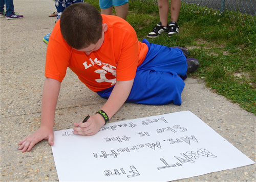Timmy Duffy, 12, writes a message on oak tag defending his brother's teacher, Jutta Marrioti.