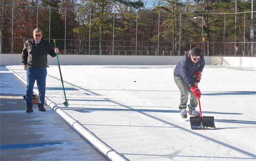 Councilman George Gabrielsen and hockey skater Justin Macdonald clearing the ice of some light snow that fell 2 days ago. (Credit: Barbaraellen Koch)