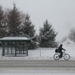 A bicyclist rides past the snow-covered sidewalk on Route 58. (Credit: Paul Squire)
