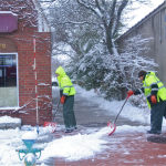 Town workers shovel snow downtown Riverhead. (Credit: Barbaraellen Koch)