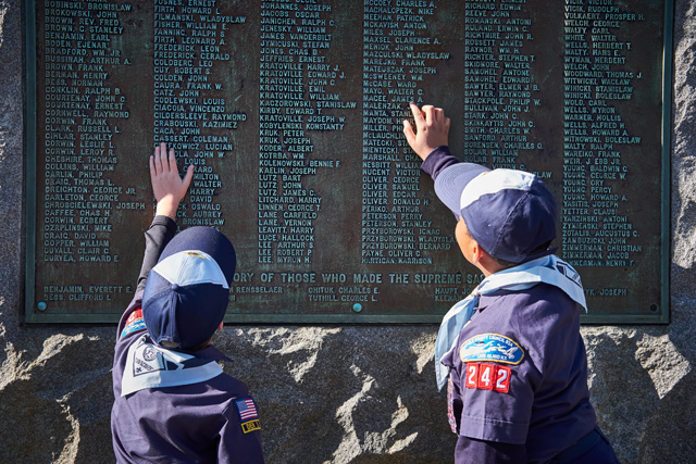 Miles Hatcher-Robertson and Lorenzo McFarlin of Cub Scouts Pack 242 examine the memorial.