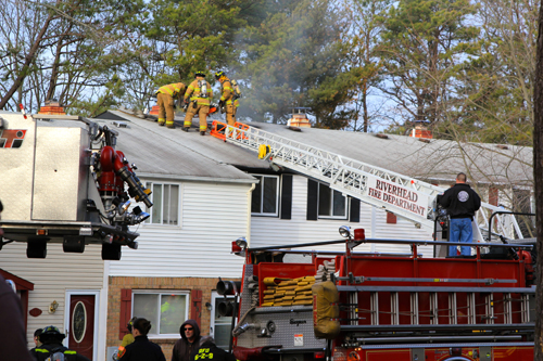 JENNIFER GUSTAVSON PHOTO | Firefighters work on the roof a Calverton home Saturday afternoon.
