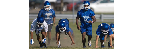 Riverhead players take part in a get-up drill during the team's first preseason practice on Monday morning. (Credit: Garret Meade)