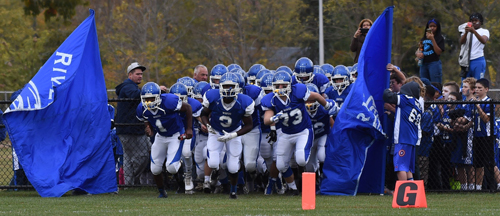 The Riverhead Blue Waves charge onto Coach Mike McKillop Memorial Field for their homecoming game against Bellport on Saturday. (Credit: Robert O'Rourk)