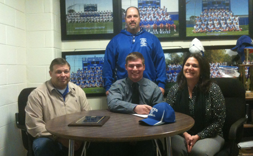 Riverhead senior lineman Eddie Willis III will play football for the United States Merchant Marine Academy. He was joined in a signing ceremony Thursday morning with his parents, Ed and Caroline, and Riverhead coach Leif Shay. (Credit: Bob Liepa)