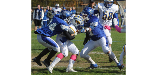 ROBERT O'ROURK PHOTO | Riverhead's Rahemm Brown, left, and Ryan Harkin wrap up West Islip's Max McNichols for a loss.