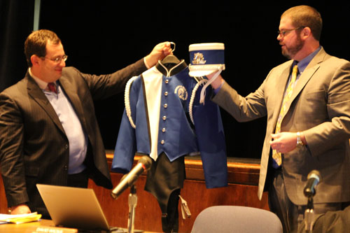 Assistant superintendents Sam Schneider, left, and David Wicks unveiling the new marching band uniforms.