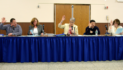JENNIFER GUSTAVSON PHOTO | Riverhead school board members voting on resolutions Tuesday night. The board also adopted the 2013-14 budget.