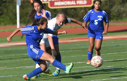 Harley Alvarado of Riverhead boots the ball while teammate Jenna Rocca looks on. (Credit: Robert O'Rourk)