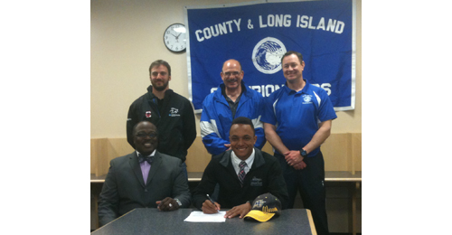 Riverhead sprinter Jacob Robinson, seated next to family friend Patrick Harris, signed to accept a scholarship from Merrimack College (Mass.). Standing, from left, are Riverhead assistant coach Will Razzano and the school's indoor and outdoor coaches, Sal Loverde and Steve Gevinski. (Credit: Bob Liepa)