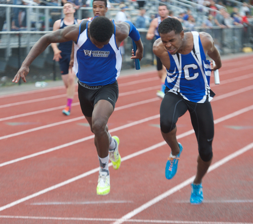 Riverhead's Steven Reid, left, leans forward at the finish line to nip a Copiague runner for victory in the 4x100-meter relay. (Credit: Robert O'Rourk)