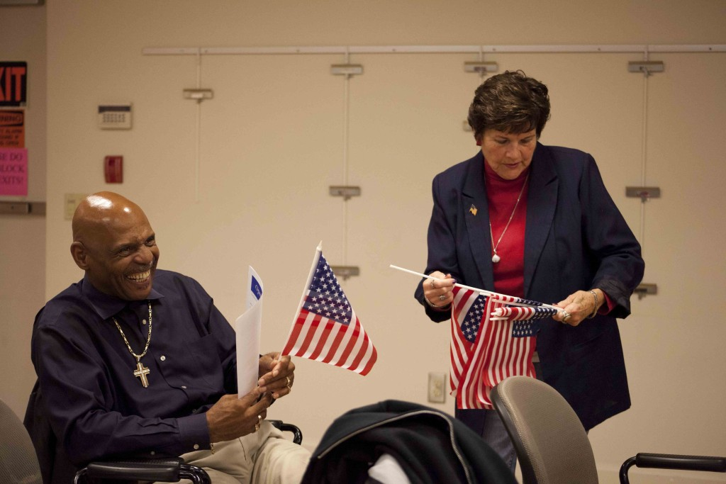 Ann Tessitor (right), a clerk with the library's senior services department, gives a flag to veteran Wilkens Young. (Credit: Chris Lisinski)