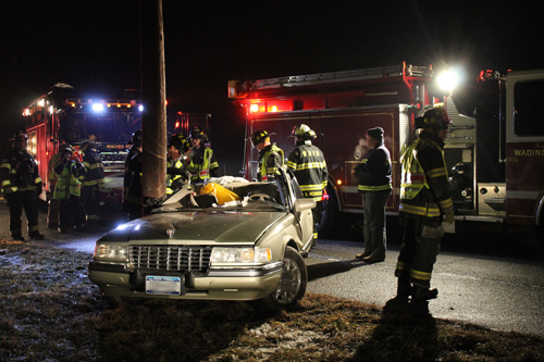 PAUL SQUIRE PHOTO | Wading River firefighters cut a man out of a crashed car late Monday night.